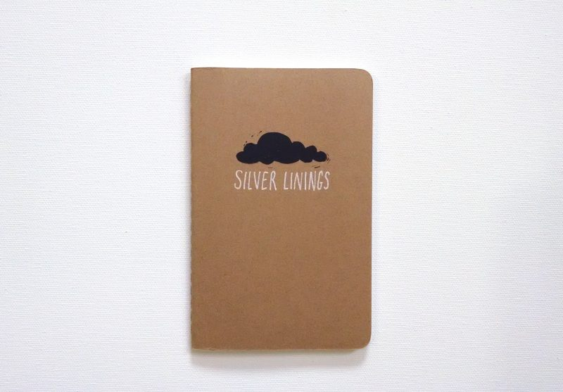 Black hand printed cloud with the words silver linings hand written beneath it on a moleskine notebook