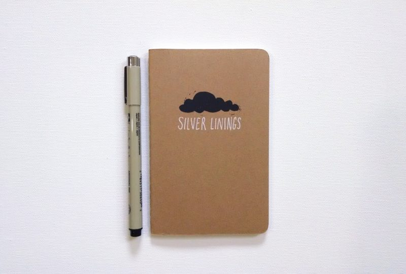 Silver linings notebook with black cloud and silver letters on a moleskine notebook with a pen