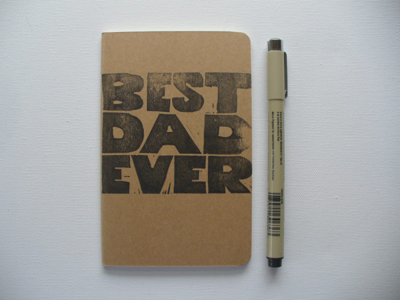 moleskine notebook hand printed with the words best dad ever in black ink