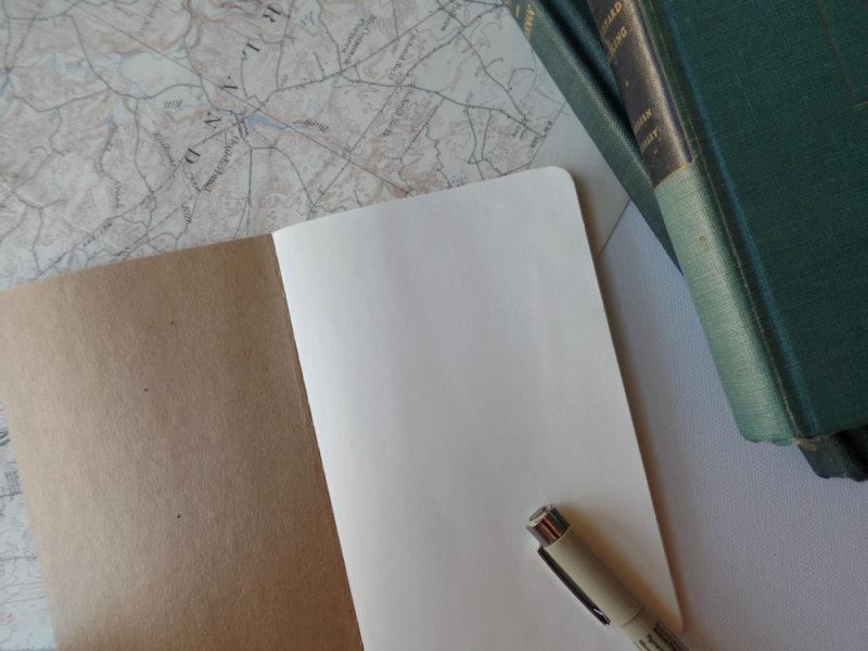 inside pages of moleskine notebook with pen vintage map and vintage books