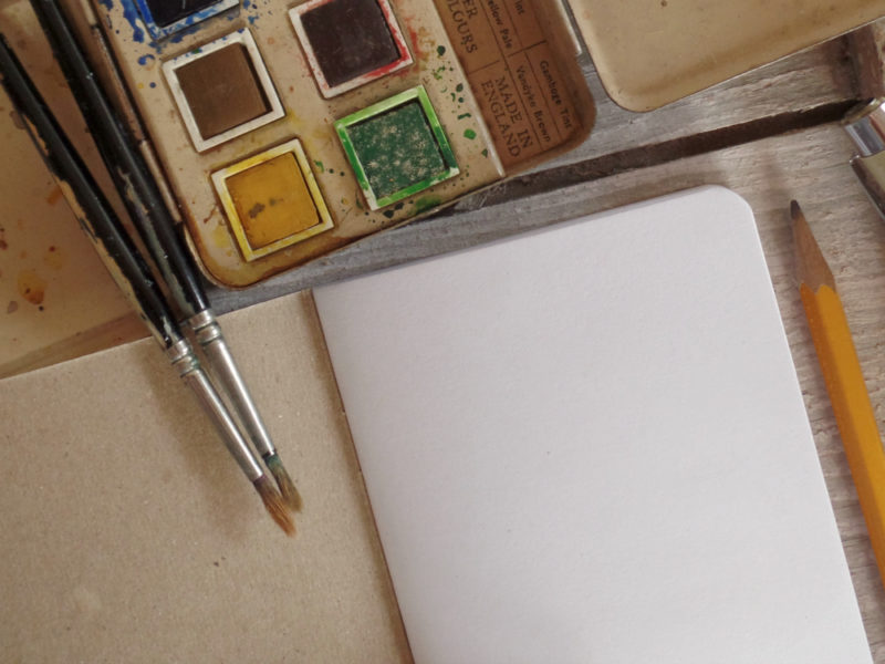 blank inside page of notebook with watercolor paint tray and brushes