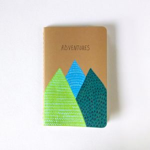 Adventures notebook with hand painted mountains in light green, blue and dark green by messy bed studio
