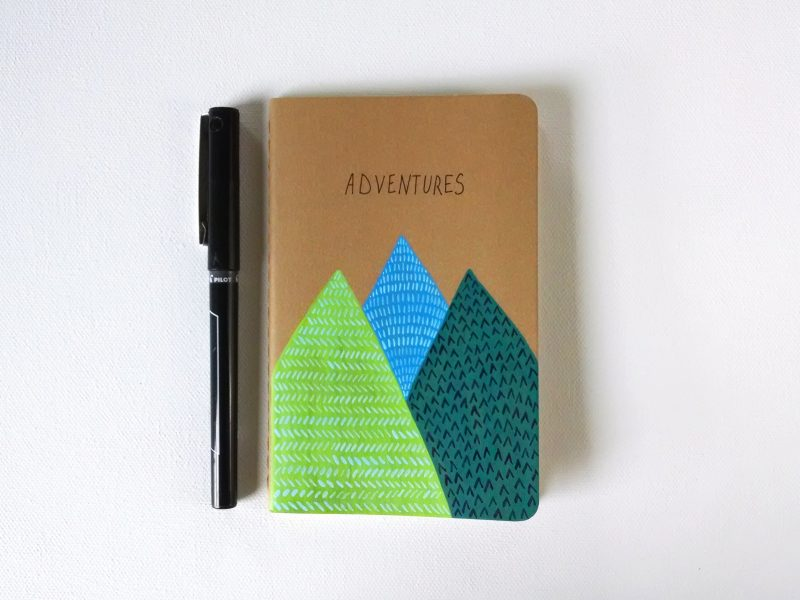 Handpainted Adventures Moleskine notebook with 3 stylized mountains shown with a pen by messy bed studio