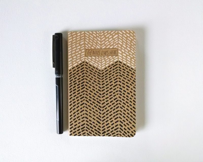 handpainted moleskine notebook with the words genius lives here in a blush and black geometric pattern by messy bed studio