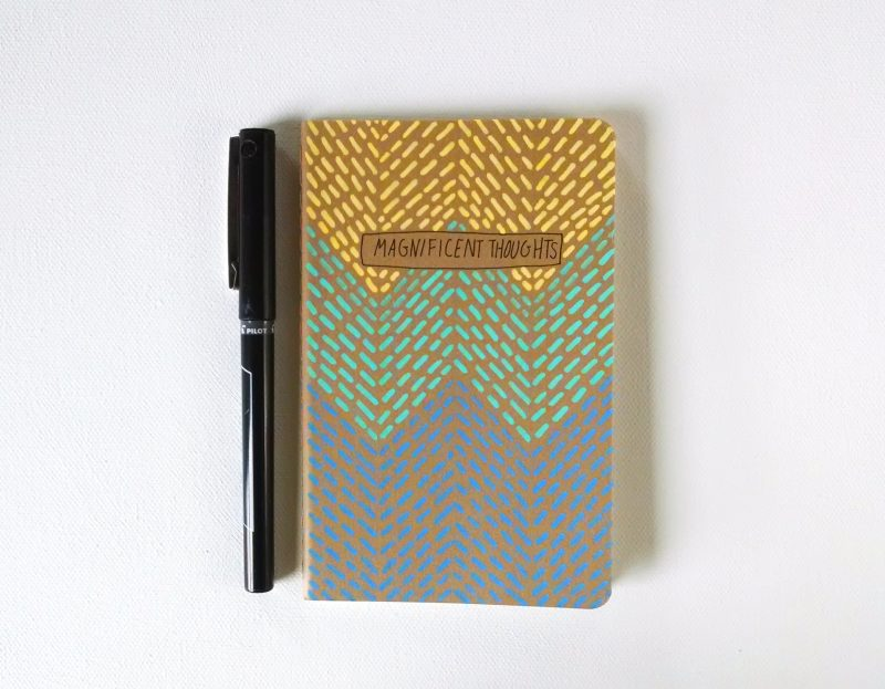 magnificent thoughts moleskine notebook handpainted in a geometric pattern in yellow, aqua and blue by messy bed studio