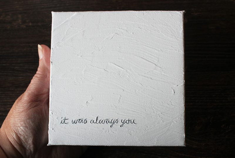 hand holding a white love note textured painting with the words - it was always you - etched into the surface by messy bed studio