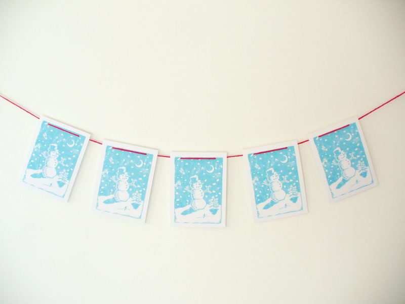 Holiday snowman garland in blue with red string