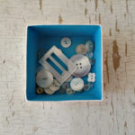 blue painted inside of keepsake box with vintage buttons