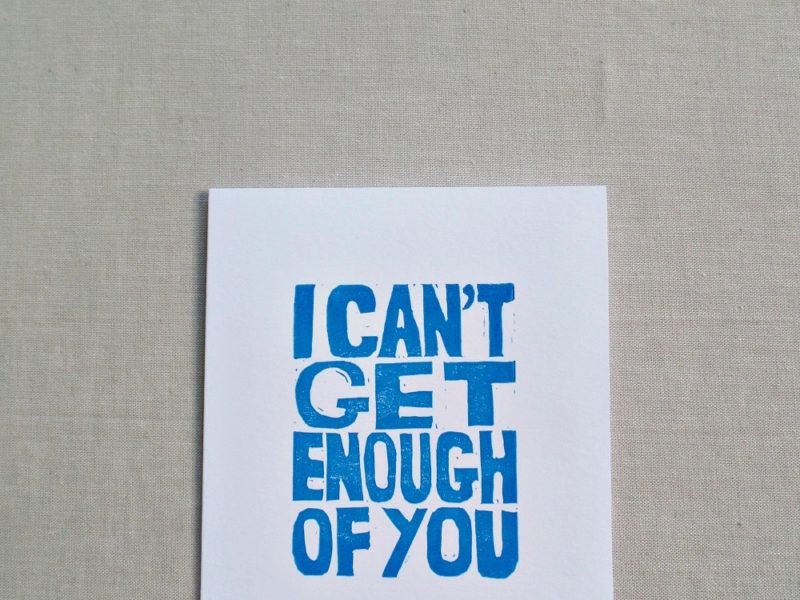 close up of hand printed card in blue ink that reads i can't get enough of you