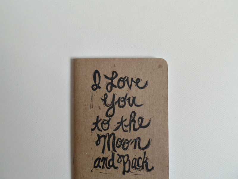 close up view of hand printed i love you to the moon and back notebook