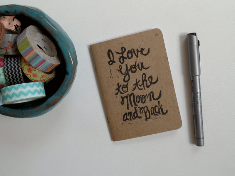 notebook printed with I love you to the moon and back with pen and washi tape