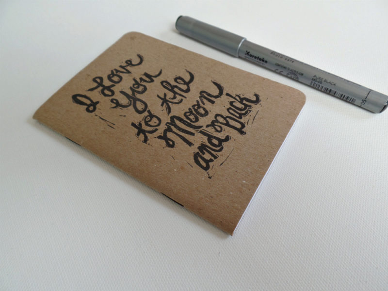 side view of i love you to the moon and back notebook with pen
