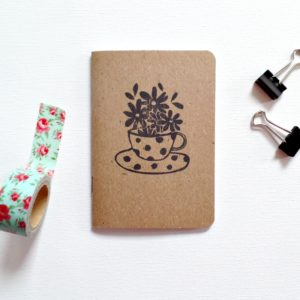 small notebook with image of tea cup and flowers with clips and washi tape