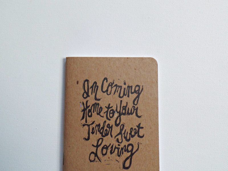 close up of hand printed notebook with coming home song lyrics