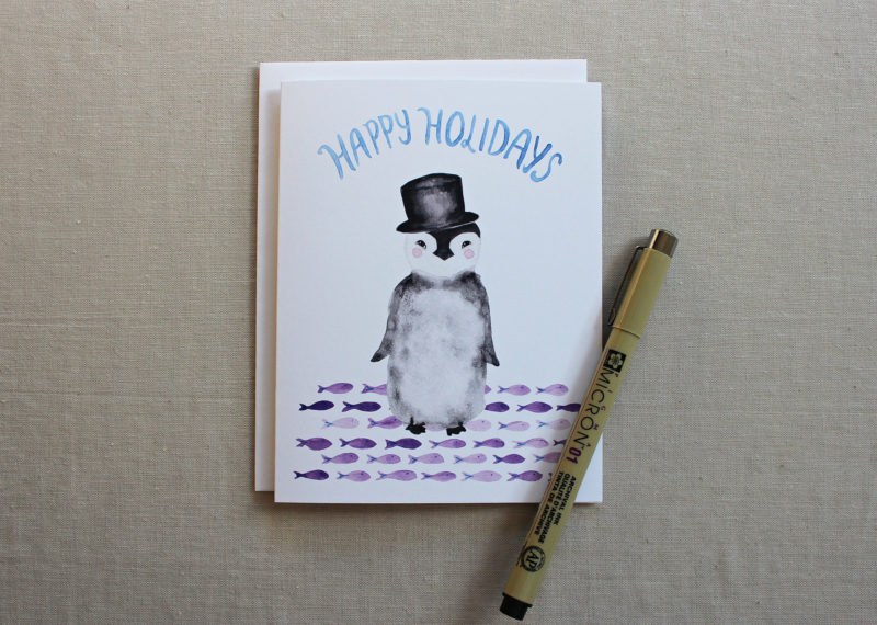 happy holidays card with penguin and fish
