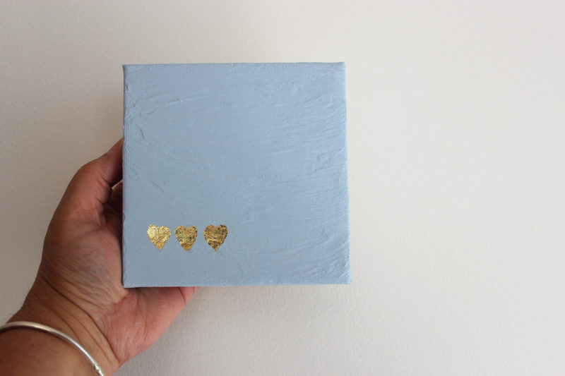 hand holding small blue canvas with gold leaf hearts