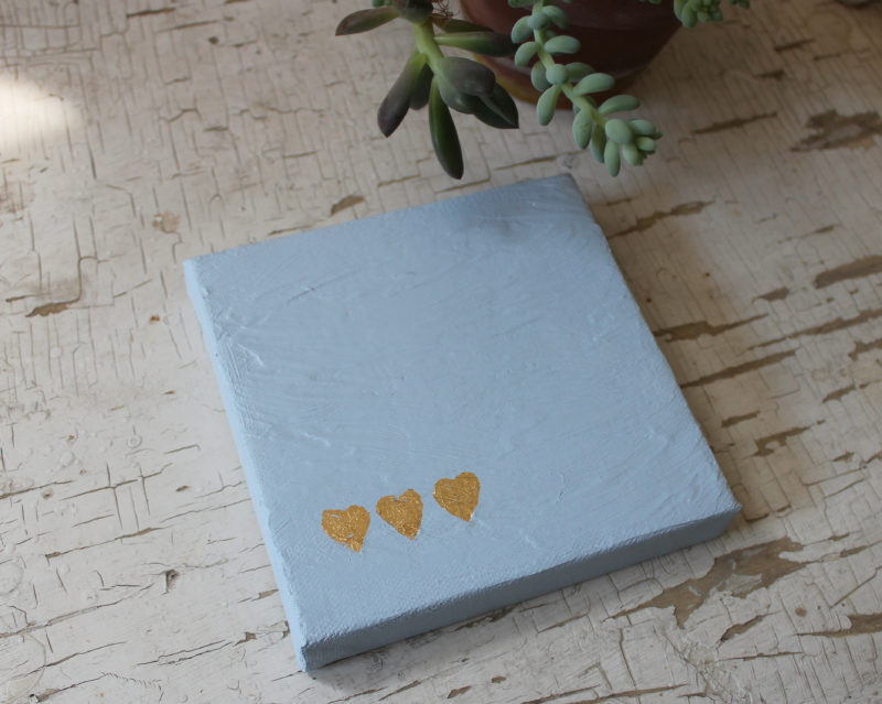 small painting with 3 gold leaf hearts with succulent plant