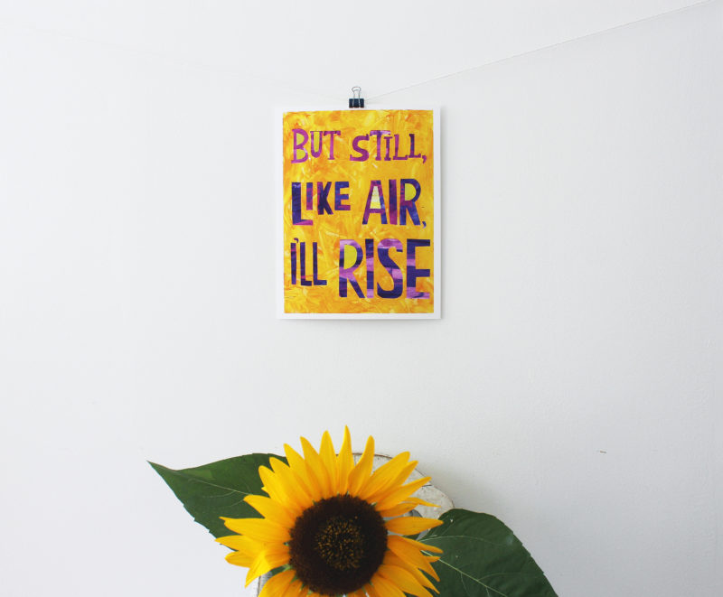 still i rise art print hanging on wall with sunflower