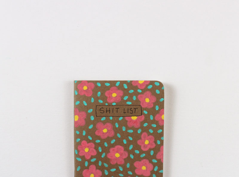 detail of hand painted floral shit list notebook