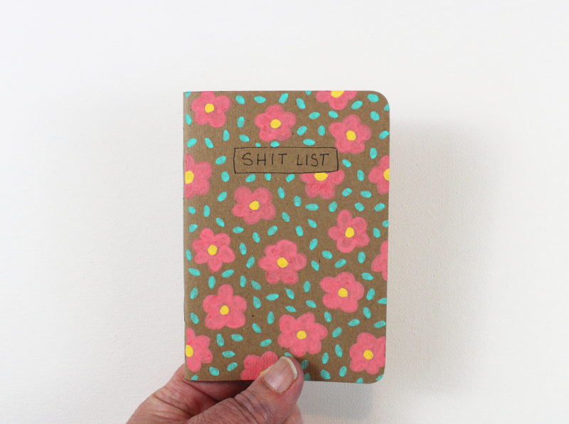 shit list notebook with flowers held in hand