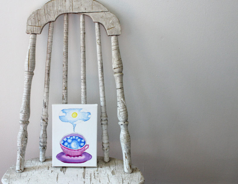 teacup full of sky original painting resting on a chair