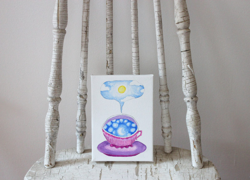 teacup full of sky watercolor painting standing on a chair