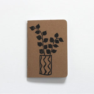 black printed houseplant in a pot on a pocket notebook