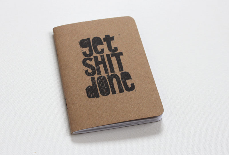 small notebook hand printed with the words get shit done in black ink