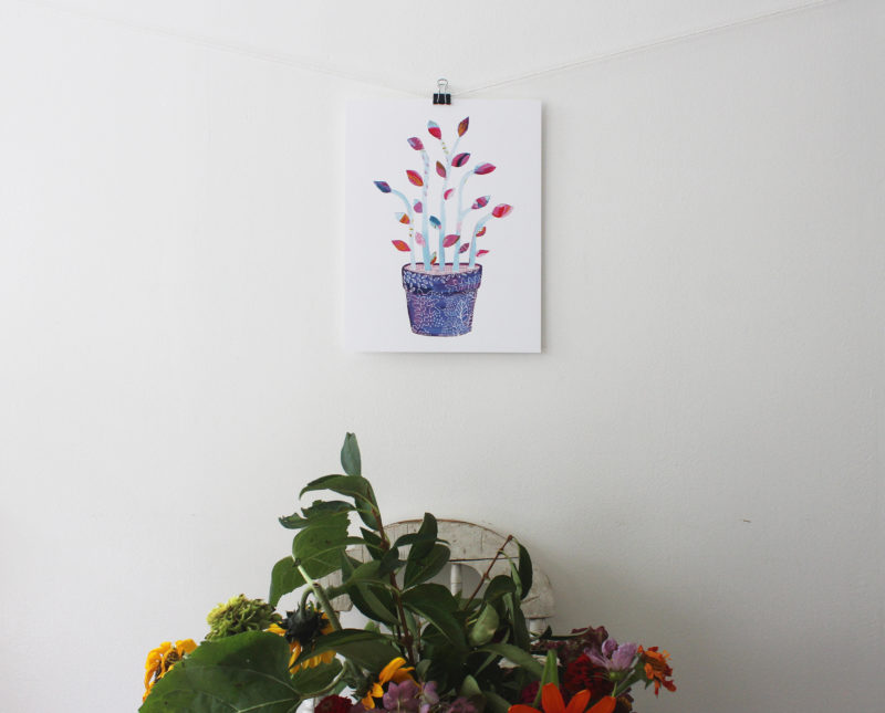 Botanical art print hung on a wall above a bouquet of flowers