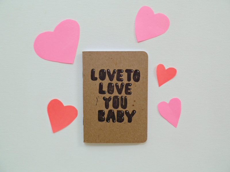 Love to love you hand printed notebook shown with pink and orange paper hearts