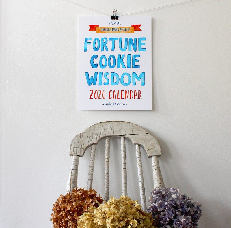A lifestyle photo of the Fortune Cookie Wisdom 2020 wall calendar hanging from a metal clip on a white wall above a farmhouse vintage chair with dried hydrangeas in copper, ivory and lavender by Messy Bed Studio