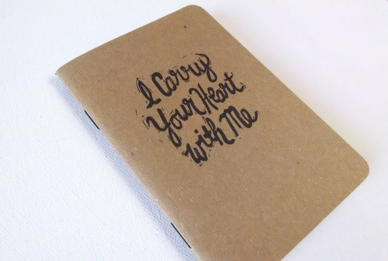 up close view showing stapled edge of I carry your heart notebook by messy bed studio