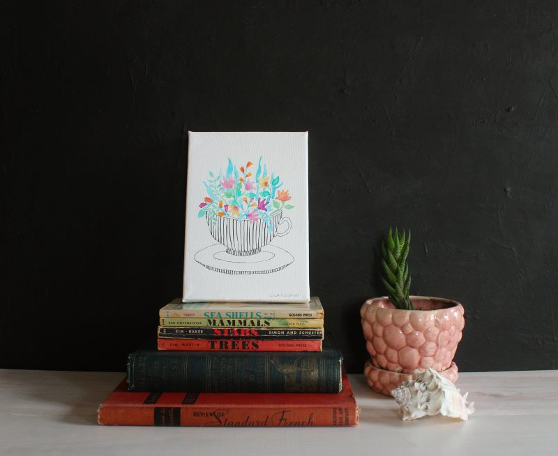 original flower watercolor painting resting on vintage books next to a plant and seashell by messy bed studio