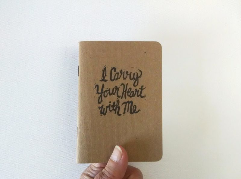 I carry your heart with me notebook held in hand by messy bed studio