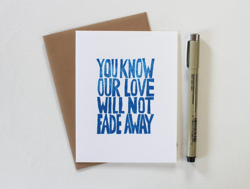 you know our love will not fade away hand printed cards in blue ink on a white card with a kraft envelope and shown with a pen by messy bed studio