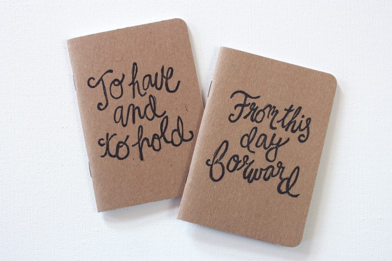hand printed pair of wedding vow books with the words to have and to hold from this day forward in black ink by messy bed studio