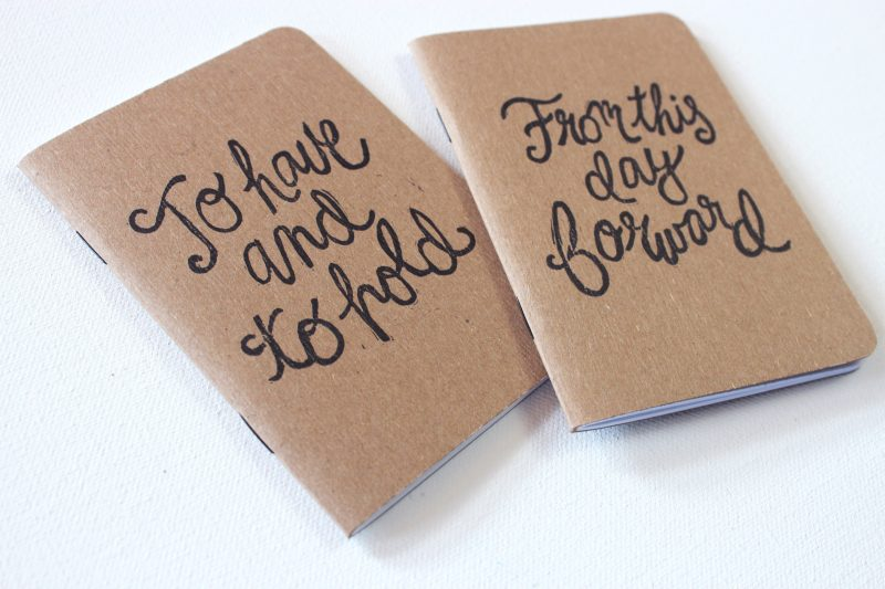 pair of hand printed vow books with the words to have and to hold in script in black ink by messy bed studio