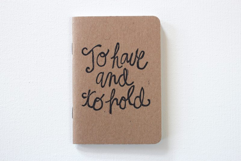 one of a pair of vow books with the words to have and to hold hand printed on kraft cover notebooks by messy bed studio