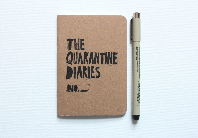 a hand printed notebook with the words - the quarantine diaries in black ink by messy bed studio