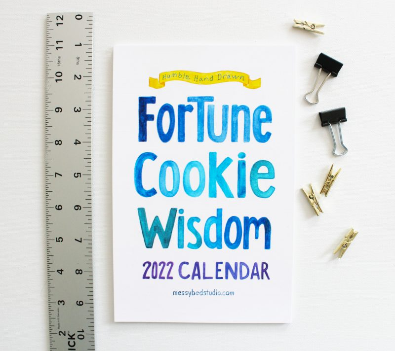 2022 Fortune Cookie Wisdom wall calendar cover with ruler and clips
